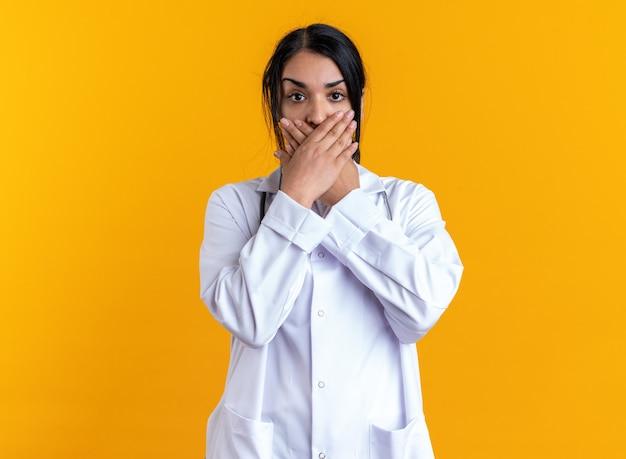 Una giovane dottoressa spaventata che indossa una tunica medica con uno stetoscopio ha coperto la bocca con le mani isolate su sfondo giallo