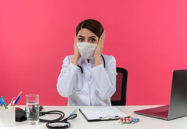 Испуганная молодая женщина-врач в медицинском халате со стетоскопом в медицинской маске, сидя за столом, работает на компьютере с медицинскими инструментами, кладя руки на голову с копией пространства