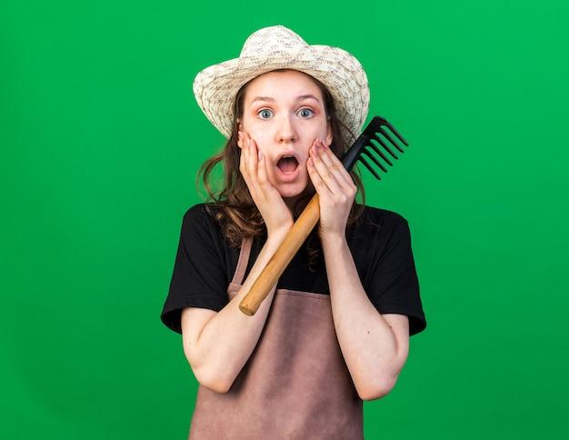 Scared young female gardener wearing gardening hat holding rake putting hands on cheeks