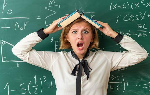 Spaventata giovane insegnante femminile in piedi di fronte lavagna coperta testa con libro in classe