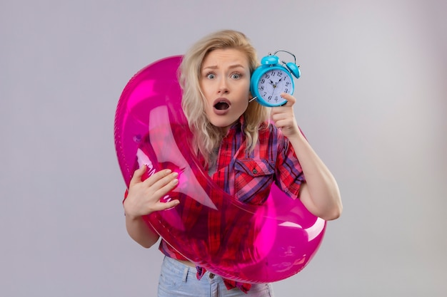 Scared young female traveler wearing red shirt in inflatable ring holding alarm clock on isolated white wall