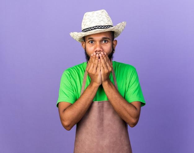 Il giovane giardiniere afroamericano spaventato che indossa il cappello da giardinaggio ha coperto la bocca con le mani