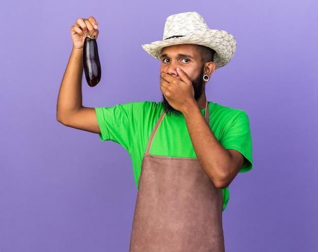 手でナスで覆われた口を保持しているガーデニングの帽子をかぶっている怖い若い庭師アフリカ系アメリカ人の男