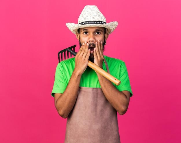 Ragazzo afroamericano del giovane giardiniere spaventato che indossa un cappello da giardinaggio che tiene la bocca coperta di rastrello con le mani isolate sul muro rosa