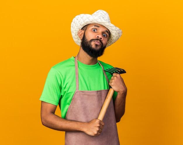 오렌지 벽에 고립 된 갈퀴를 들고 원예 모자를 쓰고 겁 먹은 젊은 정원사 아프리카계 미국인 남자