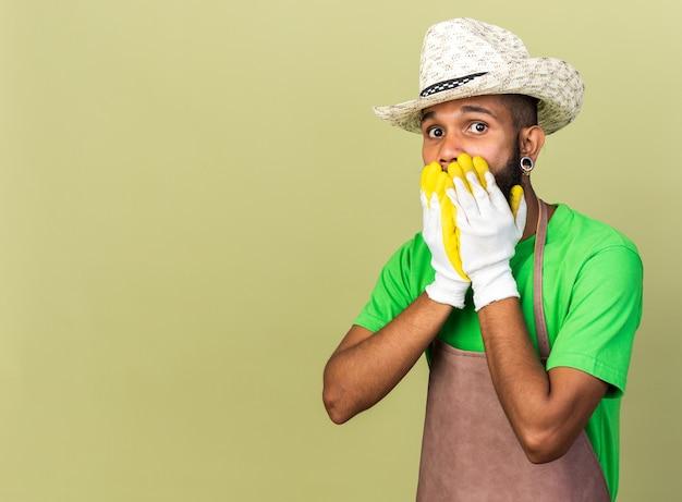 Il giovane giardiniere spaventato afroamericano che indossa un cappello da giardinaggio con guanti ha coperto la bocca con le mani