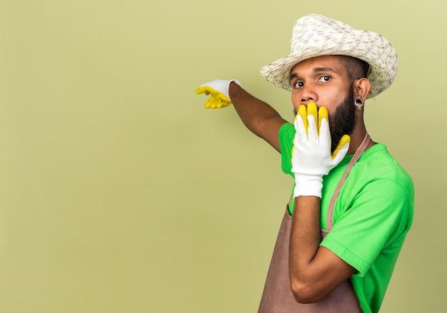 겁에 질린 젊은 정원사 아프리카계 미국인 남성이 장갑을 끼고 원예용 모자를 쓰고 올리브 녹색 벽에 복사 공간이 있는 손으로 덮인 입 뒤를 가리킵니다.