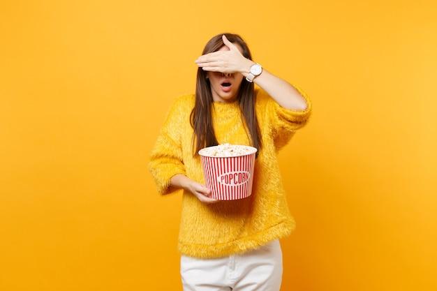 3d 아이맥스 안경을 쓴 겁에 질린 어린 소녀는 손바닥으로 얼굴을 덮고, 영화를 보고, 밝은 노란색 배경에 격리된 팝콘 양동이를 들고 있습니다. 영화, 라이프 스타일 개념에서 사람들은 진실한 감정.