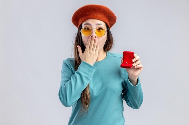 흰색 배경에 격리된 손으로 입을 덮고 결혼 반지를 들고 안경을 쓴 모자를 쓰고 발렌타인 데이에 겁 먹은 어린 소녀