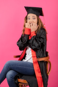 Scared young girl wearing graduation gown and bitin her nails.