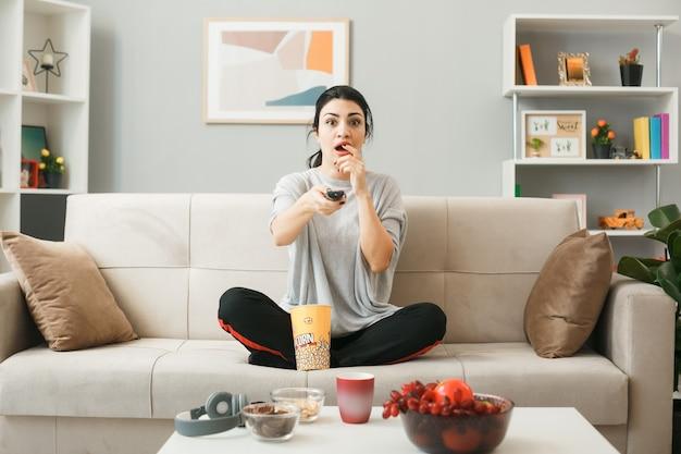 リビングルームのコーヒーテーブルの後ろのソファに座って、テレビのリモコンを保持しているポップコーンバケットを持つ怖い少女
