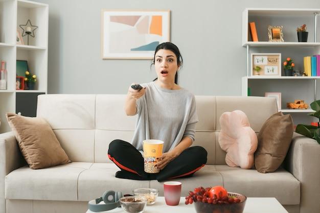Ragazza spaventata con secchio di popcorn che tiene il telecomando della tv, seduta sul divano dietro il tavolino da caffè nel soggiorno
