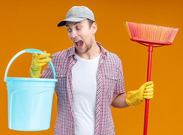 Spaventato giovane pulitore che indossa un berretto con guanti che tengono secchio e mocio isolati su una parete arancione