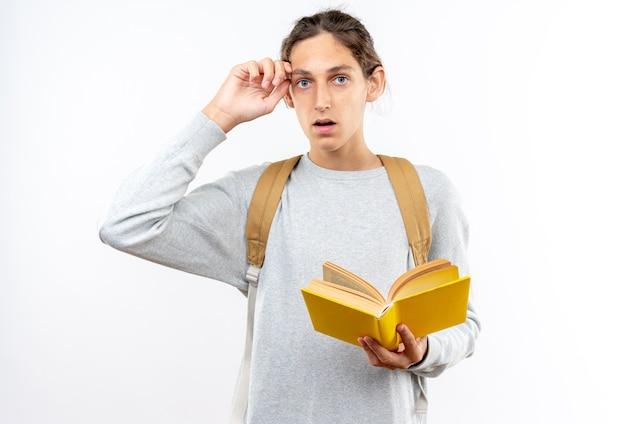 Giovane studente spaventato che indossa uno zaino che tiene il libro mettendo la mano sulla fronte isolata sul muro bianco