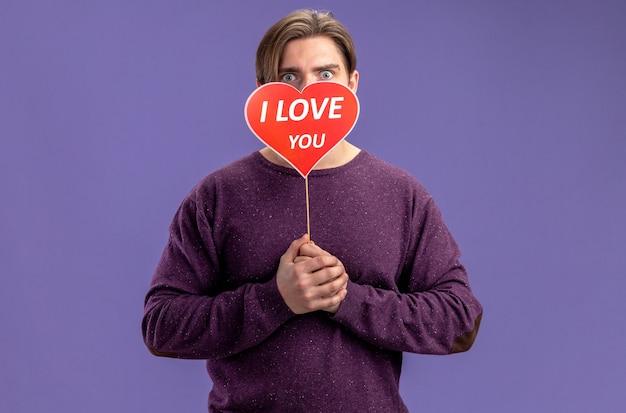 Il giovane ragazzo spaventato il giorno di san valentino ha coperto il viso con un cuore rosso su un bastone con il testo ti amo isolato su sfondo blu blue
