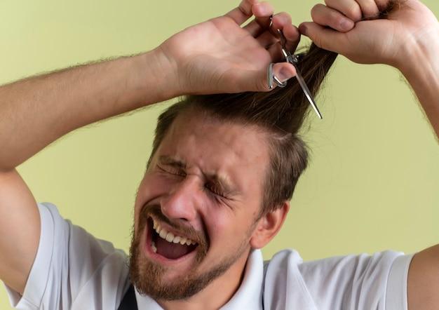 Barbiere bello giovane spaventato che taglia i suoi capelli con le forbici con gli occhi chiusi isolati sulla parete verde oliva