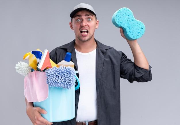 Испуганный молодой красивый уборщик в футболке и кепке, держащий ведро с чистящими инструментами и губкой, изолированным на белой стене