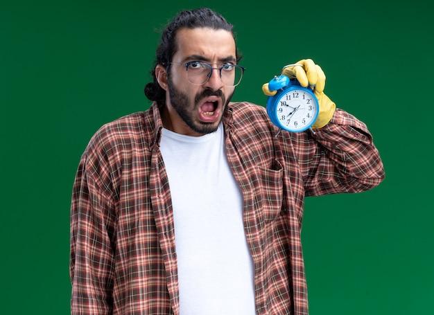 녹색 벽에 고립 된 알람 시계를 들고 t- 셔츠와 장갑을 끼고 무서 워 젊은 잘 생긴 청소 남자