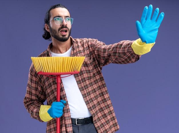 Испуганный молодой красивый уборщик в футболке и перчатках держит швабру, показывая стоп-жест, изолированный на синей стене