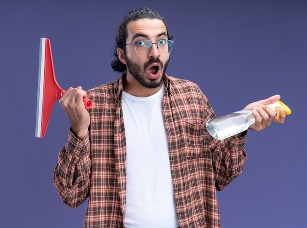 Spaventato giovane ragazzo bello delle pulizie che indossa t-shirt tenendo la testa del mop con flacone spray isolato sulla parete blu