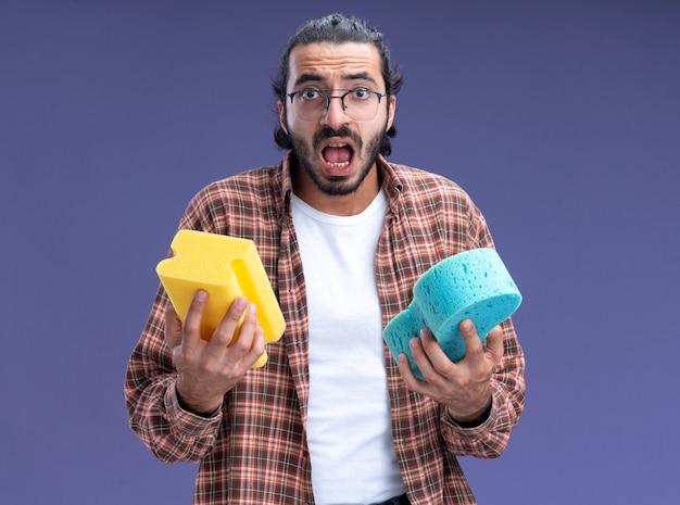 Испуганный молодой красивый уборщик в футболке с губками, изолированными на синей стене