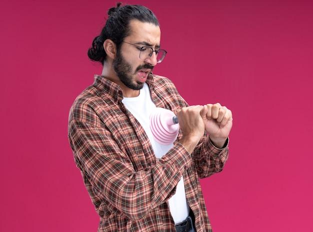 ピンクの壁に隔離された心臓にプランジャーを置くtシャツを着て怖い若いハンサムな掃除人