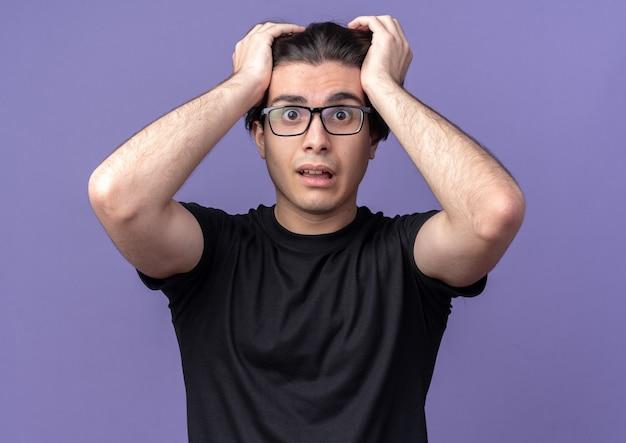 검은 티셔츠와 안경을 쓰고 무서워하는 젊은 잘 생긴 남자가 보라색 벽에 고립 된 머리를 잡고