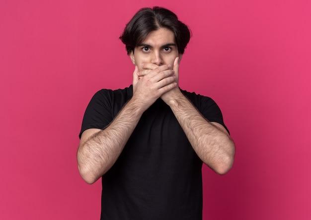 분홍색 벽에 고립 된 손으로 검은 티셔츠 덮여 입을 입고 무서 워 젊은 잘 생긴 남자