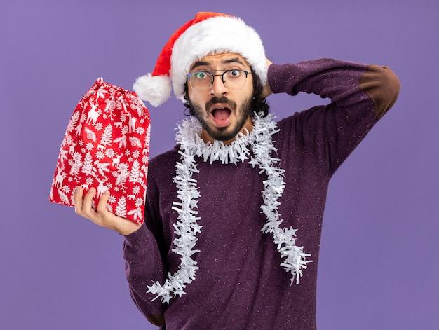 파란색 벽에 고립 된 머리 뒤에 손을 넣어 크리스마스 가방을 들고 목에 갈 랜드와 함께 크리스마스 모자를 쓰고 무서 워 젊은 잘 생긴 남자