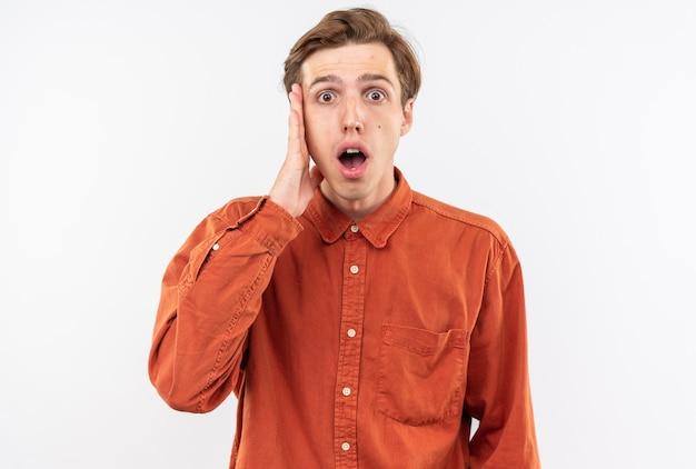Испуганный молодой красивый парень в красной рубашке положил руку на щеку
