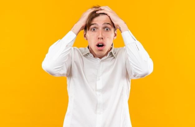 白いシャツを着て怖い若いハンサムな男はオレンジ色の壁に分離された頭をつかんだ