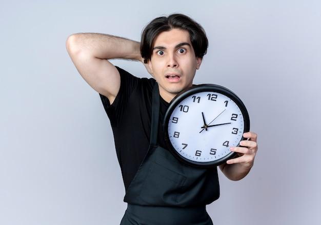 Spaventato giovane barbiere maschio bello in uniforme che tiene l'orologio da parete e mettendo la mano dietro la testa isolata sul muro bianco
