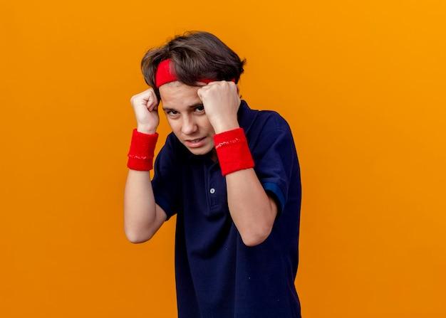 Spaventato il giovane ragazzo sportivo bello che indossa la fascia e i braccialetti con le parentesi graffe dentali che tengono i pugni vicino al fronte che esamina la parte anteriore isolata sulla parete arancione