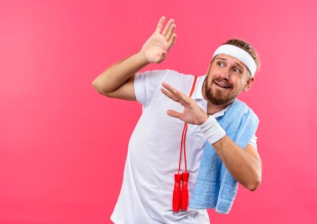 Spaventato giovane uomo sportivo bello che indossa fascia e braccialetti alzando le mani e guardando a lato con corda per saltare e asciugamano sulle spalle isolato su spazio rosa