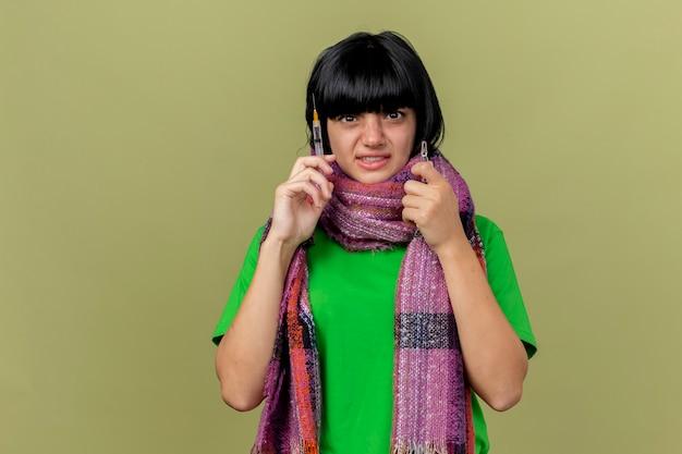 복사 공간 올리브 녹색 배경에 고립 된 카메라를 찾고 주사기와 앰플을 들고 스카프를 입고 무서 워 젊은 아픈 백인 여자