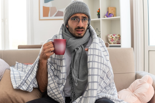 안경을 쓰고 목에 스카프를 두른 겁에 질린 젊은 백인 남자는 거실에서 소파에 앉아 컵을 가리키며 겨울 모자를 쓰고 있다