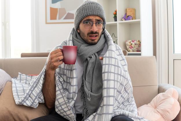 Spaventato giovane uomo caucasico malato in occhiali ottici avvolto in plaid con sciarpa intorno al collo indossando cappello invernale tenendo e indicando la tazza seduto sul divano in soggiorno