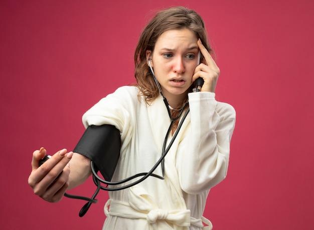 Испуганная молодая больная девушка, смотрящая в сторону, в белом халате, измеряет собственное давление с помощью сфигмоманометра, положив руку на висок, изолированный на розовом