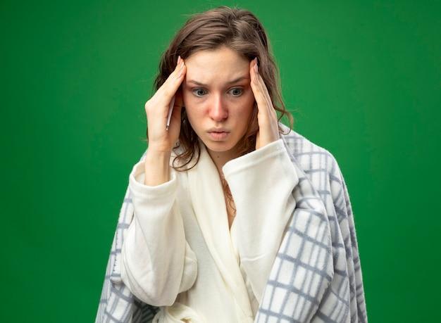 Giovane ragazza ammalata spaventata che guarda giù che indossa una veste bianca avvolta in un plaid mettendo la mano sul tempio isolato sul verde