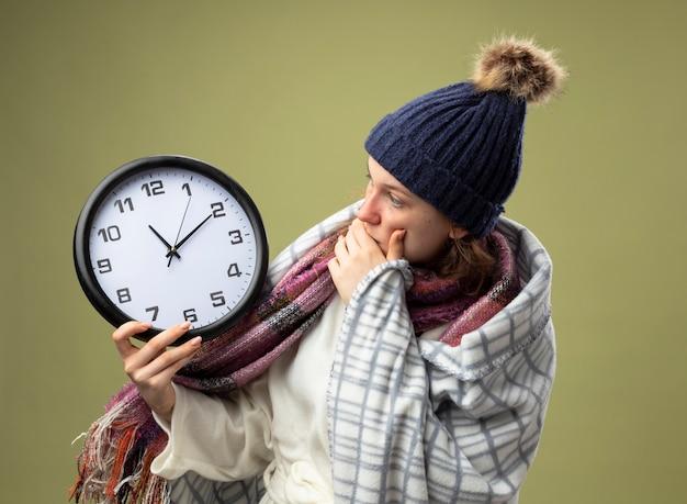 Испуганная молодая больная девушка в белом халате и зимней шапке с шарфом, держащая и смотрящая на настенные часы, завернутые в плед, изолированные на оливково-зеленом
