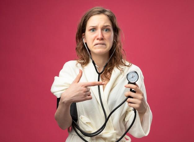 Spaventata giovane ragazza malata che indossa una veste bianca che misura la propria pressione con sfigmomanometro isolato sul rosa