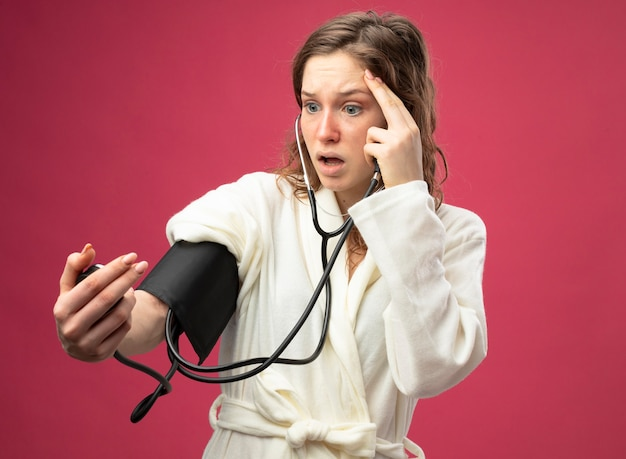 Scared young ill girl wearing white robe measuring her own pressure with sphygmomanometer putting finger on temple isolated on pink