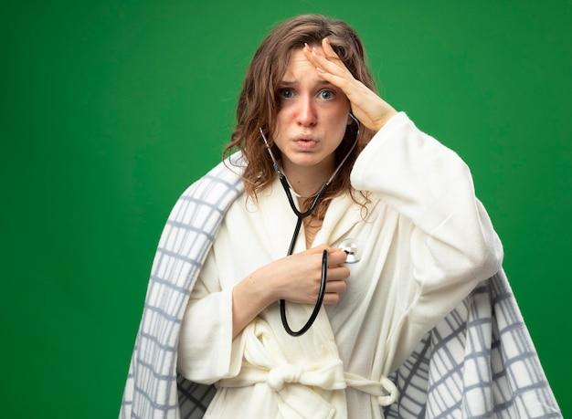 Spaventata giovane ragazza malata che indossa una veste bianca avvolta in un plaid ascoltando il proprio battito cardiaco mettendo la mano sulla fronte isolato su verde