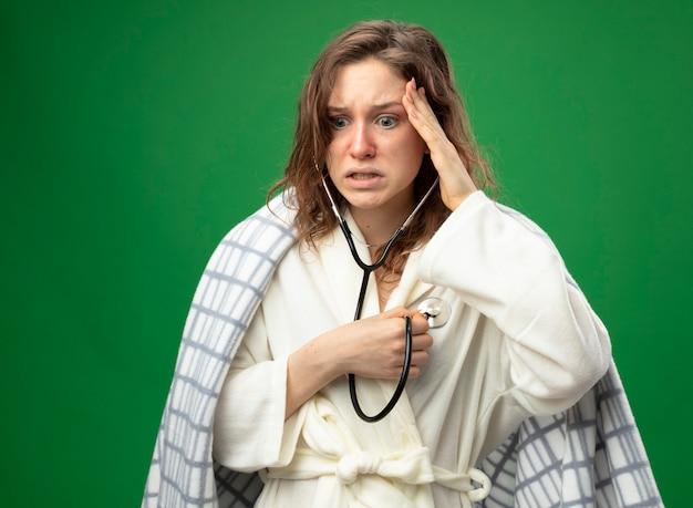 Spaventata giovane ragazza malata che indossa una veste bianca avvolta in un plaid ascoltando il proprio battito cardiaco mettendo la mano sul tempio isolato sul verde