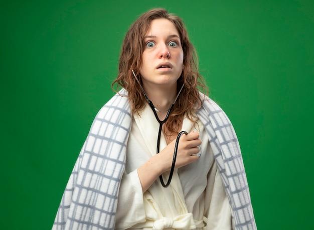 Giovane ragazza ammalata spaventata che indossa una veste bianca avvolta in un plaid che ascolta il proprio battito cardiaco con lo stetoscopio isolato sul verde Foto Gratuite
