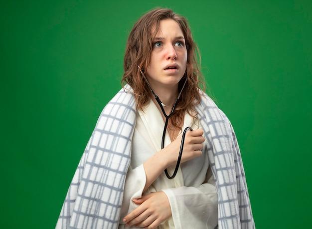 Giovane ragazza ammalata spaventata che indossa una veste bianca avvolta in un plaid che ascolta il proprio battito cardiaco con lo stetoscopio isolato sul verde