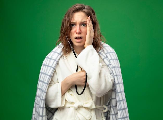 Spaventata giovane ragazza malata che indossa una veste bianca avvolta in un plaid ascoltando il proprio battito cardiaco con uno stetoscopio mettendo la mano sulla guancia isolato su verde