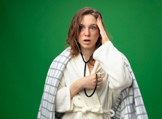 Spaventata giovane ragazza malata che indossa una veste bianca avvolta in un plaid ascoltando il proprio battito cardiaco con uno stetoscopio mettendo la mano sulla testa isolata su verde