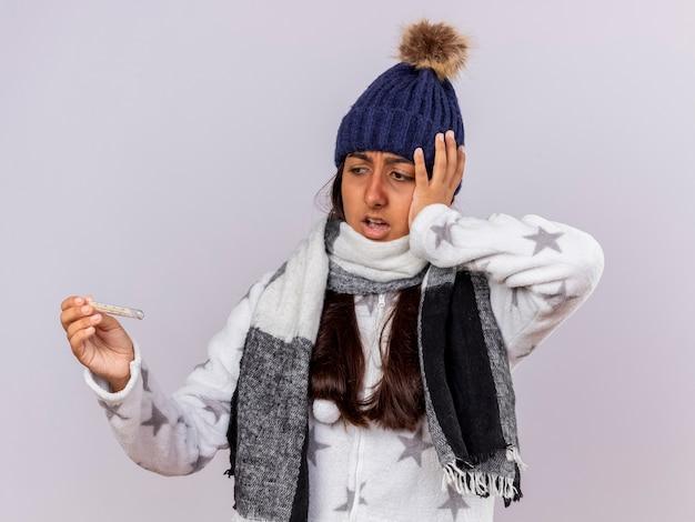 スカーフを保持し、白い背景で隔離の頭に手を置いて温度計を見て冬の帽子をかぶって怖い若い病気の女の子
