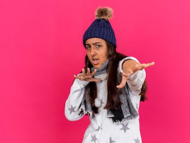 Giovane ragazza ammalata spaventata che porta il cappello di inverno con la sciarpa che tiene fuori le mani isolate sul colore rosa